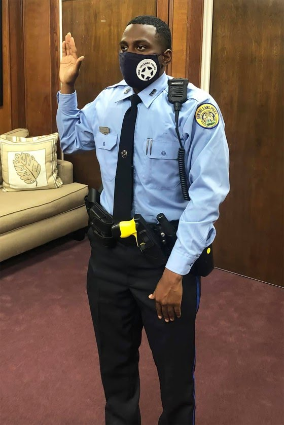 Image: Recruit Mark Hall Jr. raises his hand as hi is administered the oath of office to become a police officer, following in his father's footsteps.